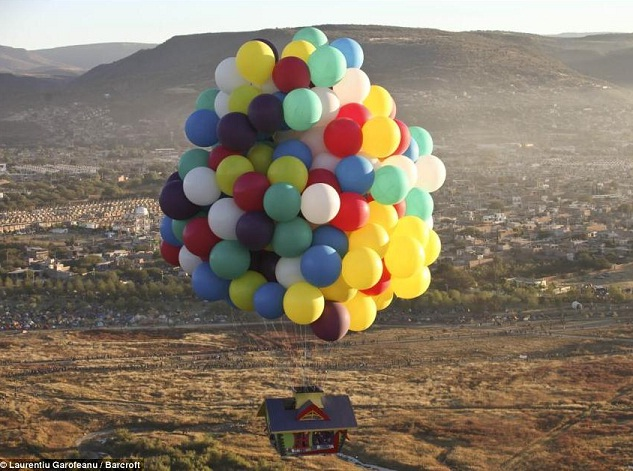 a house floating in the air by balloons